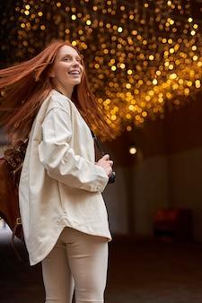 Giovane donna hipster in giacca beige che cammina in una strada cittadina. avere buon umore sopra il bokeh festivo incandescente. ghirlande luci sfondo urbano. ritratto di signora rossa in abbigliamento casual con capelli volanti