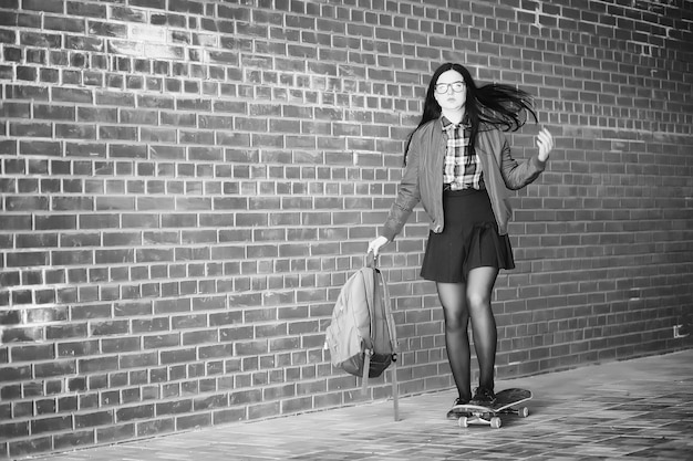 Una giovane ragazza hipster sta cavalcando uno skateboard. amiche ragazze per una passeggiata in città con uno skateboard. sport primaverili in strada con lo skateboard. Foto Premium