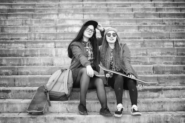 Una giovane ragazza hipster sta cavalcando uno skateboard. amiche ragazze per una passeggiata in città con uno skateboard. sport primaverili in strada con lo skateboard.