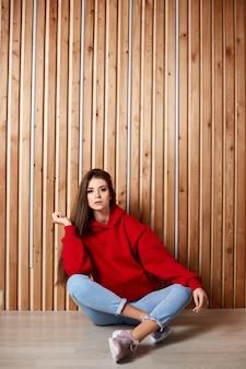 Una giovane ragazza hipster in una felpa con cappuccio rossa e blue jeans si siede sul pavimento sopra una parete di legno.