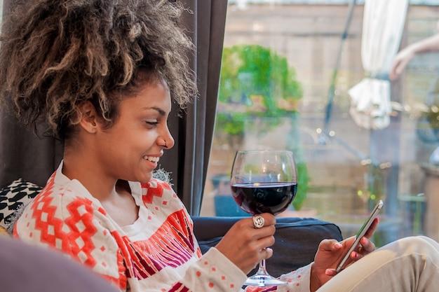 Giovane, hipster, ragazza, usando, moderno, smartphone, dispositivo, seduto, a casa, comunicazione, amici, in, social network, freelance, femmina, lavoro, casa, felicità, godimento