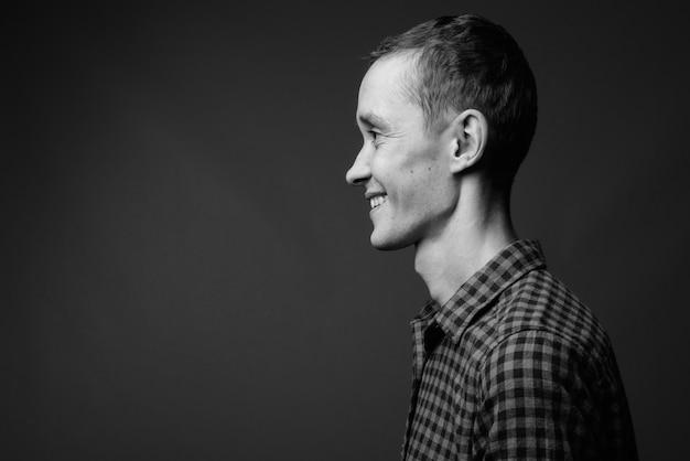 Uomo giovane hipster contro il muro grigio in bianco e nero
