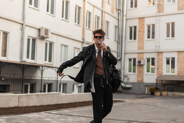 Uomo giovane hipster in occhiali da sole alla moda in una giacca di pelle in jeans con uno zaino in posa e fuma per strada vicino a edifici d'epoca. un modello alla moda in abiti oversize si diverte a fumare.