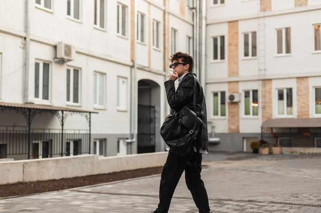 Giovane uomo hipster in occhiali da sole alla moda in un abbigliamento elegante con uno zaino in posa e fuma per strada vicino a edifici d'epoca. un modello moderno in abiti oversize si diverte a fumare. pausa sigaretta