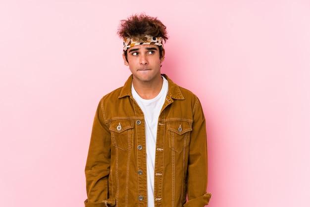 Uomo giovane hipster isolato giovane che va a un festival confuso, si sente dubbioso e incerto.