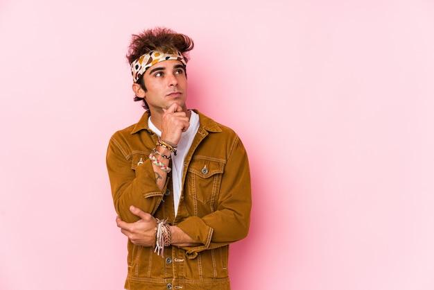 Uomo giovane hipster isolato giovane che va a un festival guardando lateralmente con espressione dubbiosa e scettica.