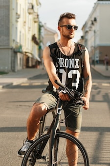 Uomo giovane hipster con bicicletta seduto su una bicicletta
