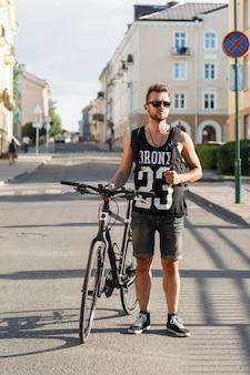 Uomo giovane hipster con bicicletta a piedi in città