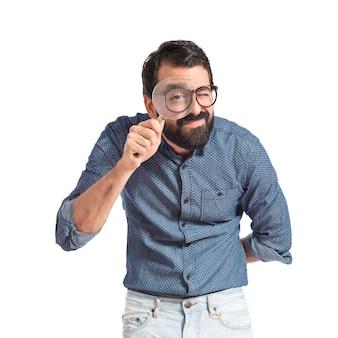 Uomo giovane hipster con lente di ingrandimento