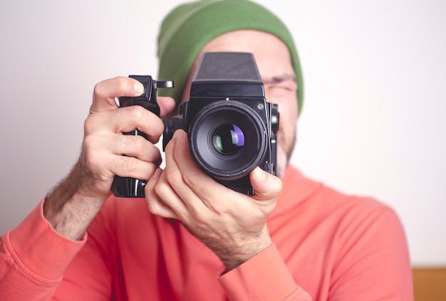 Uomo giovane hipster con vecchia fotocamera a pellicola vintage.