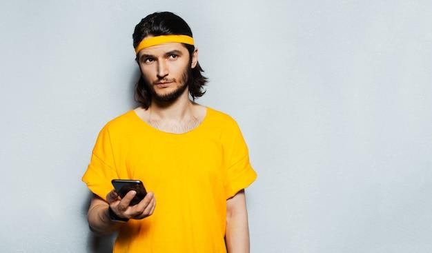 Giovane hipster in giallo che tiene smartphone e distoglie lo sguardo, su grigio.