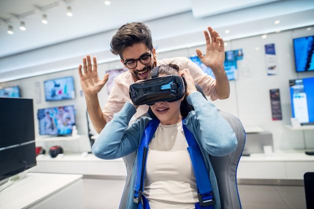 Coppia stupita giocosa dei giovani pantaloni a vita bassa divertendosi con gli occhiali di protezione di vr mentre ragazza che si siede sulla sedia nel negozio di tecnologia.