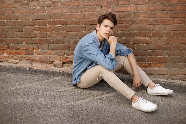Il giovane hipster si siede nella sua camicia di jeans blu abbottonata che mostra una t-shirt di cotone bianca senza etichetta contro uno sfondo di muro di mattoni