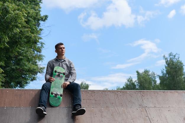 Il giovane skateboarder hipster si siede sulla base delle montagne russe da skate nel parco sullo sfondo del cielo estivo e degli alberi verdi sfocati in una giornata calda