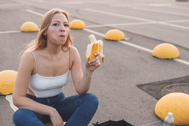 Giovane donna sportiva hipster che si prende una pausa dallo skate che corre mangiando banana