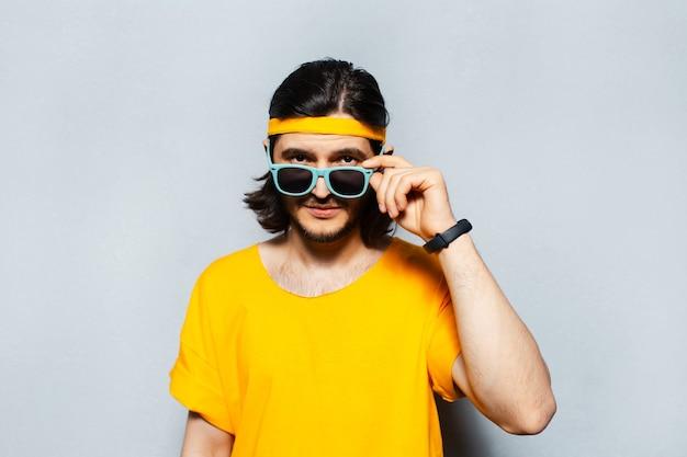 Giovane hipster indossando occhiali da sole e maglietta gialla su sfondo grigio.