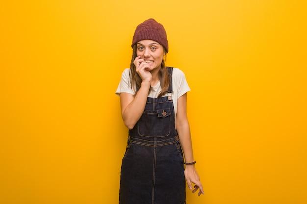 Giovane donna hipster morde le unghie, nervosa e molto ansiosa
