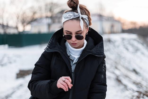 Giovane donna hipster in occhiali da sole neri in un cappotto invernale nero con uno zaino in pelle alla moda con una bandana in un maglione bianco
