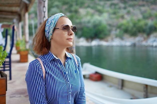 Donna giovane hipster godendo sole e buona giornata calda durante il suo tempo di ricreazione