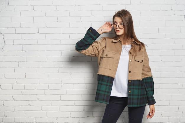 Donna giovane hipster in occhiali sopra il muro di mattoni bianchi. ritratto con copyspace.