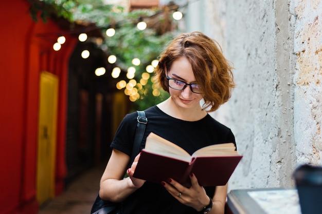 Giovane donna hipster in bicchieri con tagli di capelli corti leggendo il libro in caffè all'aperto di strada