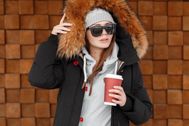 Giovane donna hipster in un cappello grigio lavorato a maglia in un'elegante giacca invernale con pelliccia in una calda felpa blu che tiene una tazza di caffè vicino alla parete di legno. abiti invernali