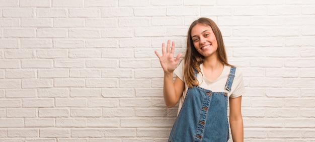 Donna giovane hipster che mostra il numero cinque