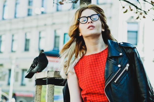 Giovane donna hipster che indossa un abito rosso in città. primavera e uccelli colombe.