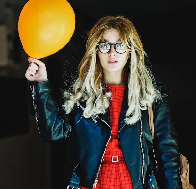 Giovane donna hipster con palloncino in città, tempo di primavera