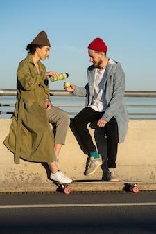 Giovani hipsters coppia skateboarder versano il tè dal thermos sul ponte indossando abiti casual alla moda