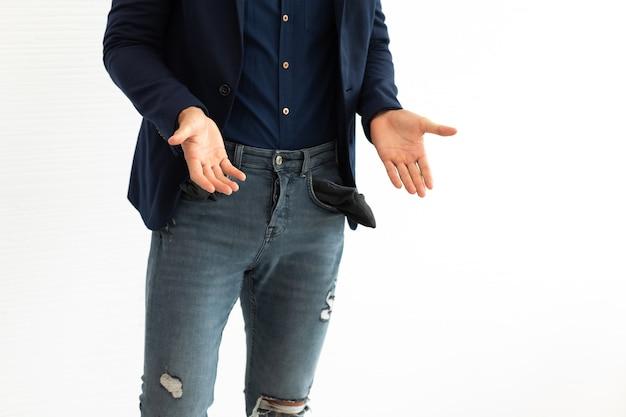 Giovane libero professionista ispanico dell'uomo di affari che mostra le sue tasche vuote che stanno sul fondo bianco.