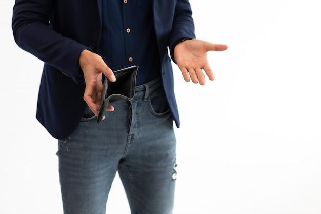 Giovane libero professionista ispanico dell'uomo di affari che mostra il suo portafoglio vuoto nelle mani che stanno sul fondo bianco.