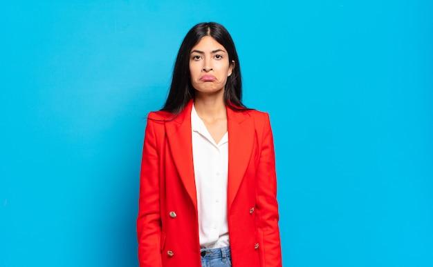Giovane imprenditrice ispanica che si sente triste e stressata, sconvolta a causa di una brutta sorpresa, con uno sguardo negativo e ansioso
