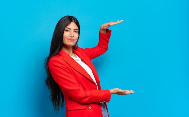 Giovane imprenditrice ispanica che tiene un oggetto con entrambe le mani sullo spazio della copia laterale, mostrando, offrendo o pubblicizzando un oggetto