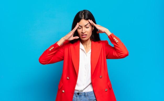 Giovane imprenditrice ispanica che sembra stressata e frustrata, lavora sotto pressione con mal di testa e turbata da problemi