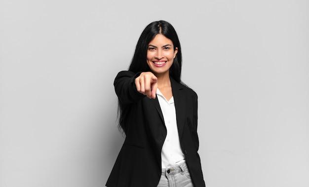 Giovane imprenditrice ispanica che punta alla telecamera con un sorriso soddisfatto, fiducioso, amichevole, scegliendo te