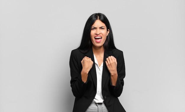 Giovane imprenditrice ispanica che grida in modo aggressivo con sguardo infastidito, frustrato, arrabbiato e pugni stretti, sentendosi furioso
