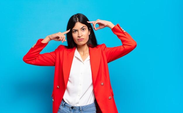 Giovane imprenditrice ispanica con uno sguardo serio e concentrato, brainstorming e pensando a un problema impegnativo