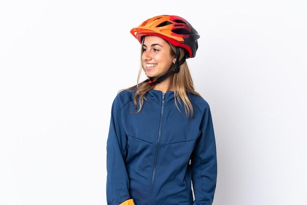 Donna giovane ciclista ispanica isolata su bianco che osserva al lato e che sorride
