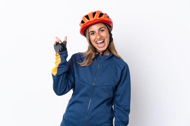Giovane donna ispanica ciclista isolata su bianco sorridendo e mostrando il segno di vittoria