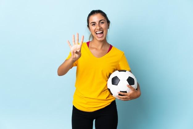 Giovane donna ispanica del giocatore di football americano più isolata sul blu felice e che conta quattro con le dita