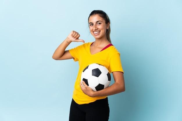 Donna giovane giocatore di football americano ispanico sopra isolata sulla parete blu orgogliosa e soddisfatta