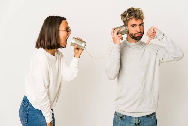 Giovani amici ispanici che parlano attraverso un sistema di barattolo di latta che mostra un gesto di antipatia, i pollici verso il basso. concetto di disaccordo.