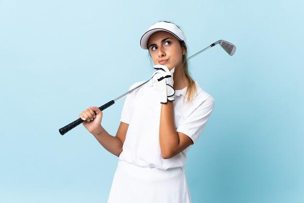 Giovane donna ispanica del golfista sopra la parete blu isolata e che osserva in su