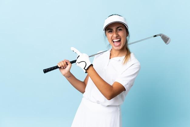Giovane donna ispanica del golfista sopra la parete blu isolata che indica il dito al lato e che presenta un prodotto