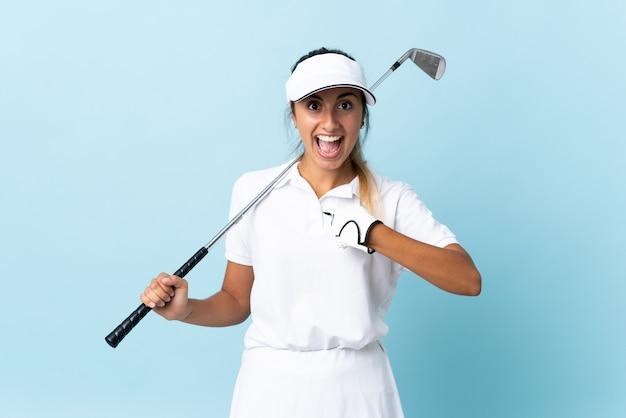 Giovane donna ispanica del golfista sopra la parete blu isolata con l'espressione facciale di sorpresa