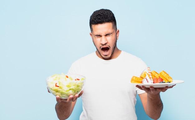 Espressione arrabbiata del giovane uomo ispanico e concetto stante a dieta
