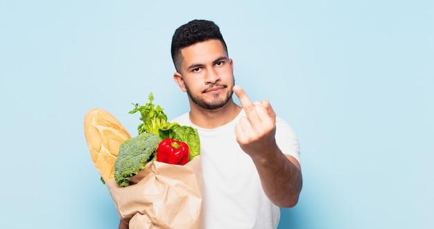 Espressione arrabbiata del giovane uomo ispanico. concetto di acquisto di verdure