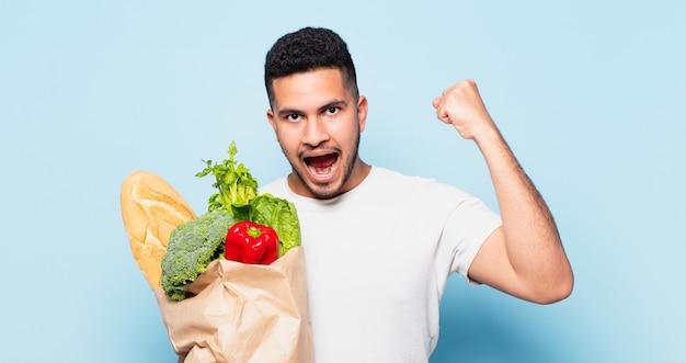 Giovane uomo ispanico che celebra con successo una vittoria. concetto di acquisto di verdure