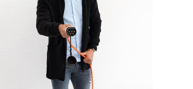 Il giovane ispanico ha caricato l'automobile elettrica dalla spina dell'automobile elettrica. spina della tenuta dell'uomo della mano isolata su fondo bianco.